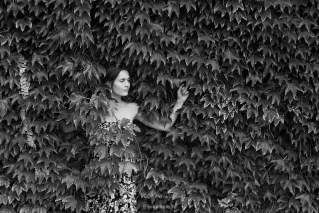 portrait of a beautiful woman leaning into a hedge