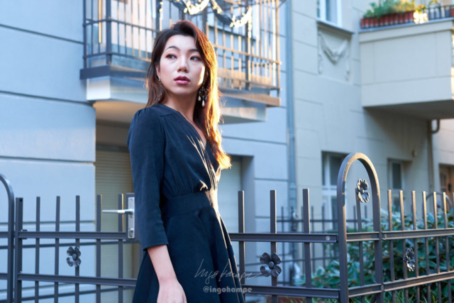 portrait of a beautiful womans standing in front of a residential building during golden hour